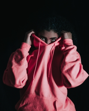 african american girl holding up hoodie over her face